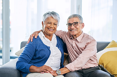 Buy stock photo Cropped portrait of an affectionate senior couple smiling while sitting together on the sofa in the living room