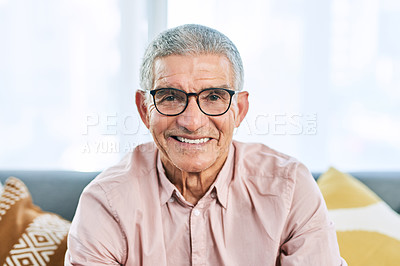 Buy stock photo Cropped portrait of a retired senior man smiling while sitting on the sofa in the living room