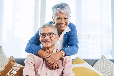 Buy stock photo Cropped portrait of an affectionate senior couple smiling at the camera in the living room during the day
