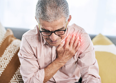 Buy stock photo Cropped shot of an unhappy senior man suffering from chest pain while sitting on the sofa during the day
