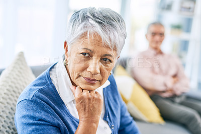 Buy stock photo Cropped shot of a retired senior woman looking away while sitting on the sofa in their living room