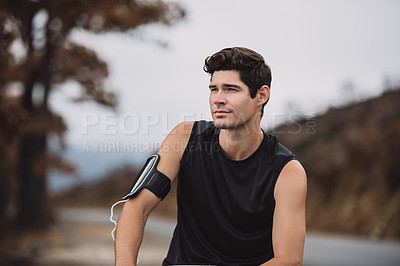 Buy stock photo Shot of a sporty young man taking a break while exercising outdoors