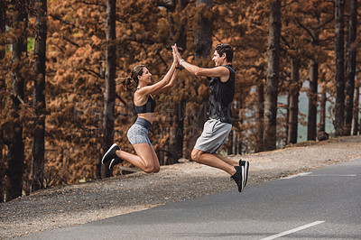 Buy stock photo Shot of a sporty young couple giving each other a high five while exercising together outdoors