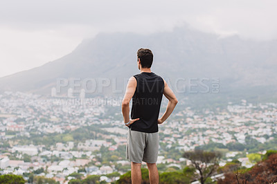 Buy stock photo Rearview shot of a sporty young man looking at the view while exercising outdoors