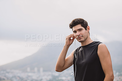 Buy stock photo Portrait of a sporty young man listening to music while exercising outdoors
