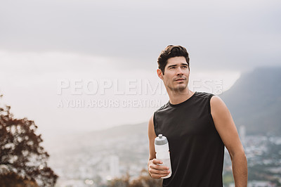 Buy stock photo Shot of a sporty young man holding a bottle of water while exercising outdoors