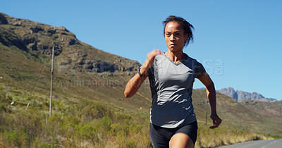Buy stock photo Shot of a sporty young woman running outdoors against a mountain background
