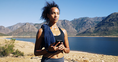 Buy stock photo Shot of a sporty young woman using her cellphone while out for a run in nature