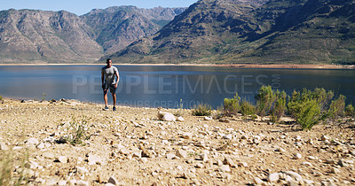 Buy stock photo Shot of a sporty young man out for a run in nature