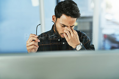 Buy stock photo Shot of a handsome young businessman suffering from a headache while working on a computer in his office