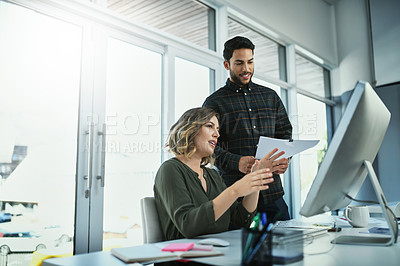 Buy stock photo Shot of two young businesspeople working on a computer together in an office