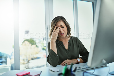 Buy stock photo Shot of an attractive young businesswoman suffering from a headache while working in her office