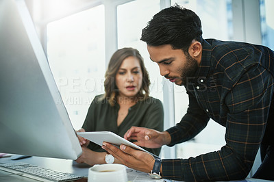 Buy stock photo Shot of two young businesspeople using a digital tablet together in their office