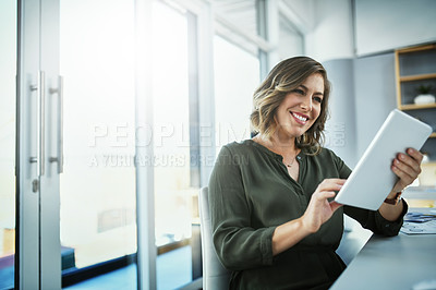 Buy stock photo Shot of an attractive young businesswoman using a digital tablet in her office
