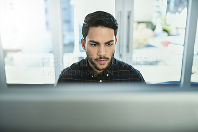 Buy stock photo Shot of a handsome young businessman working on a computer in his office