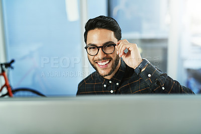 Buy stock photo Portrait of a handsome young businessman working on a computer in his office