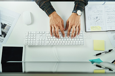 Buy stock photo High angle shot of an unrecognizable businessman typing on a computer keyboard at his office desk