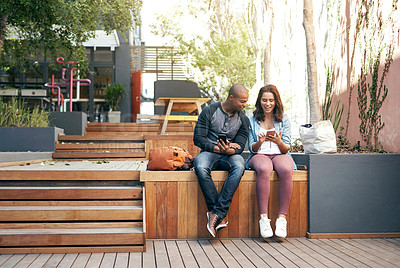 Buy stock photo Shot of a young man and woman using their smartphones outside on campus