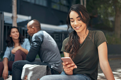 Buy stock photo Shot of a young woman using her smartphone outside on campus