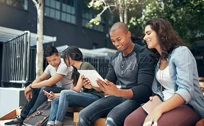 Buy stock photo Shot of a young man and woman using a digital tablet together on campus