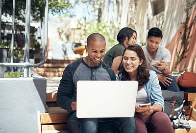 Buy stock photo Shot of a young man and woman using a laptop together on campus