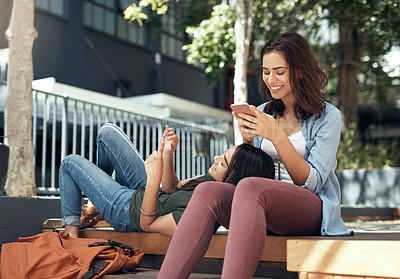 Buy stock photo Shot of two young women using  their smartphones on campus
