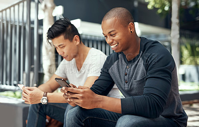 Buy stock photo Shot of two young men using  their smartphones on campus