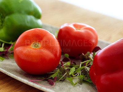 Buy stock photo Shot of brightly coloured tomatoes arranged on a silver dish before being cooked in the kitchen during the day