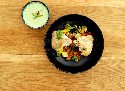 Buy stock photo Aerial shot of a delicious bowl of guacamole and grilled chicken and vegetables in the kitchen during the day