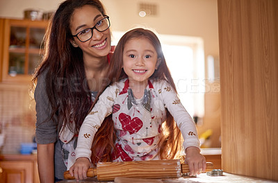 Buy stock photo Portrait of a mother and her little daughter baking together at home