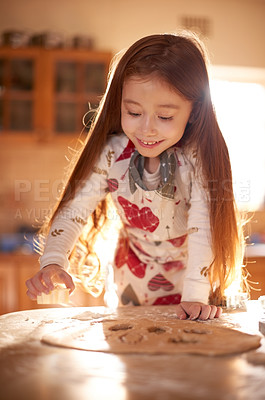 Buy stock photo Shot of an adorable little girl baking at home