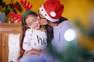 Buy stock photo Shot of a young woman kissing her daughter on the cheek on Christmas