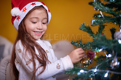 Buy stock photo Cropped shot of a little girl decorating a Christmas tree