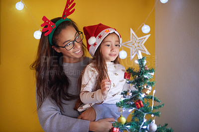 Buy stock photo Shot of a little girl and her mother decorating a Christmas tree