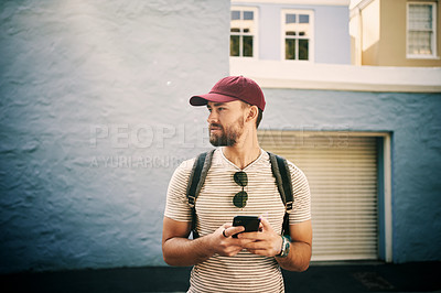 Buy stock photo Cropped shot of a handsome young man standing alone and holding his cellphone in the city during the day