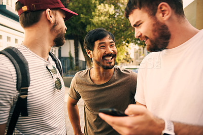 Buy stock photo Cropped shot of three handsome young men standing together in the street and using a cellphone during the day