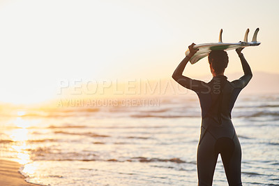 Buy stock photo Rearview shot of a female surfer carrying her surfboard over her head at the beach