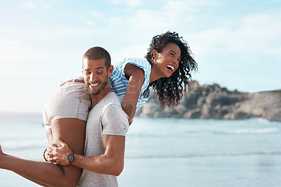 Buy stock photo Shot of a young couple enjoying some quality time together at the beach