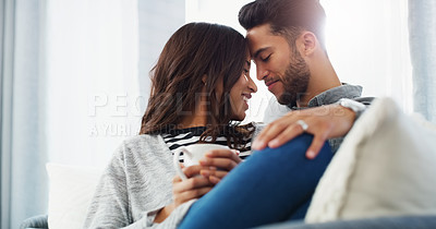 Buy stock photo Cropped shot of an affectionate young couple cuddling with each other while in their living room during the day