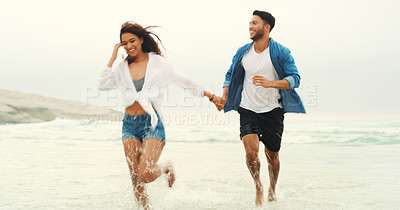 Buy stock photo Full length shot of an affectionate young couple holding hands and running through the water at the beach