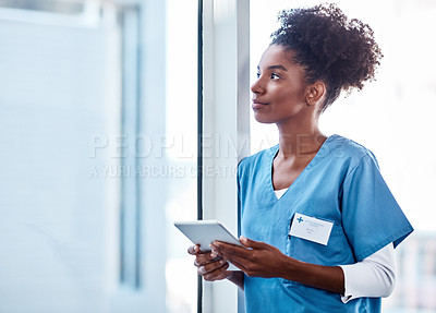 Buy stock photo Shot of a young doctor using a digital tablet in a hospital and looking away thoughtfully