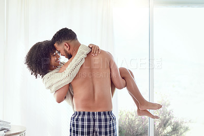 Buy stock photo Rearview shot of an affectionate young man carrying his wife in their bedroom at home