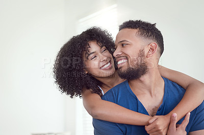 Buy stock photo Cropped shot of an affectionate young woman hugging her husband from behind in their bedroom at home