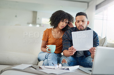 Buy stock photo Shot of a young couple looking stressed while going over their finances at home
