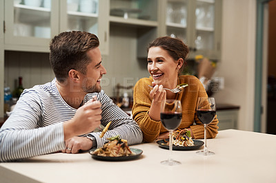 Buy stock photo Shot of an affectionate young couple smiling at each other while enjoying dinner in their kitchen at home