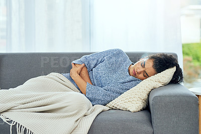 Buy stock photo Shot of a young woman experiencing stomach pain on the sofa at home