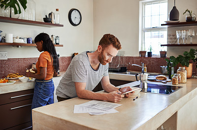 Buy stock photo Shot of a young man using a digital tablet while his girlfriend is cooking in the background