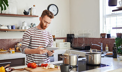Buy stock photo Shot of a man using a digital tablet while cooking at home