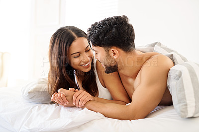 Buy stock photo Shot of a carefree young couple relaxing on the bed together at home during the morning hours