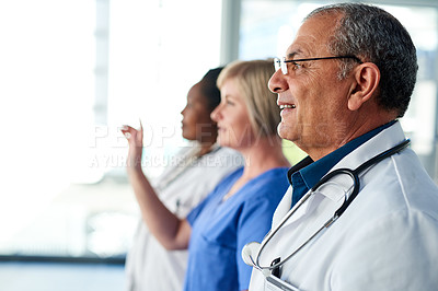 Buy stock photo Cropped shot of three medical practitioners standing in the hospital